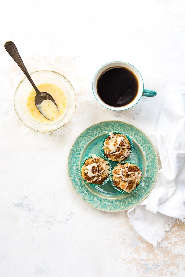 Three Coffee Cake Muffins on a blue plate with a cup of coffee and small bowl of fresh orange glaze with vintage spoon