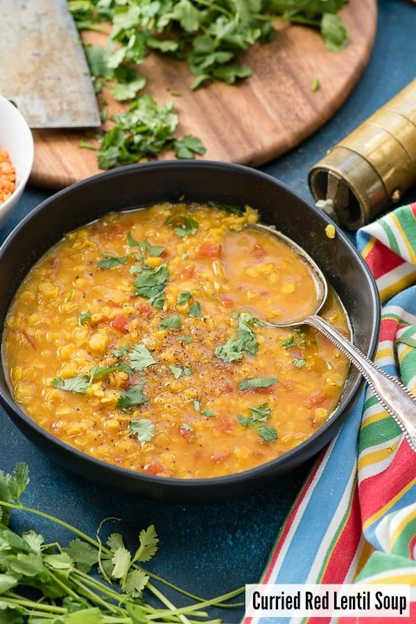 Curried Red Lentil Soup with torn cilantro in a black bowl with striped napkin