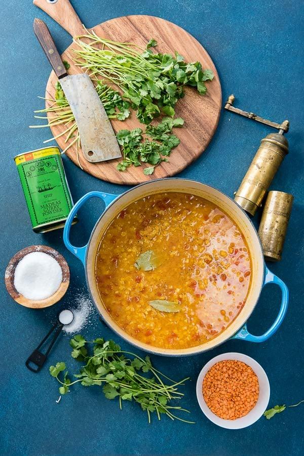 Blue enamel pot of Curried Red Lentil Soup with chopped cilantro, kosher salt pot, pepper grinder