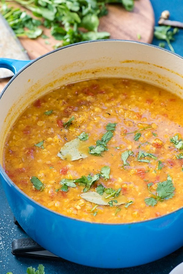 French-blue enamel pot of Curried Red Lentil Soup with torn cilantro leaves