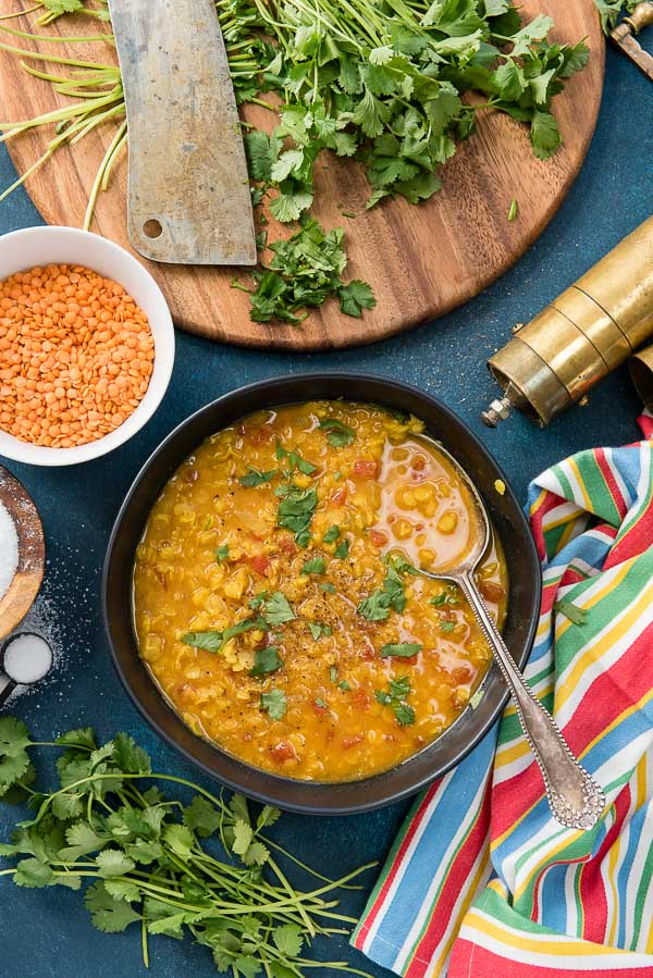 Steamy black bowl of Curried Red Lentil Soup with antique spoon, pepper grinder and striped napkin