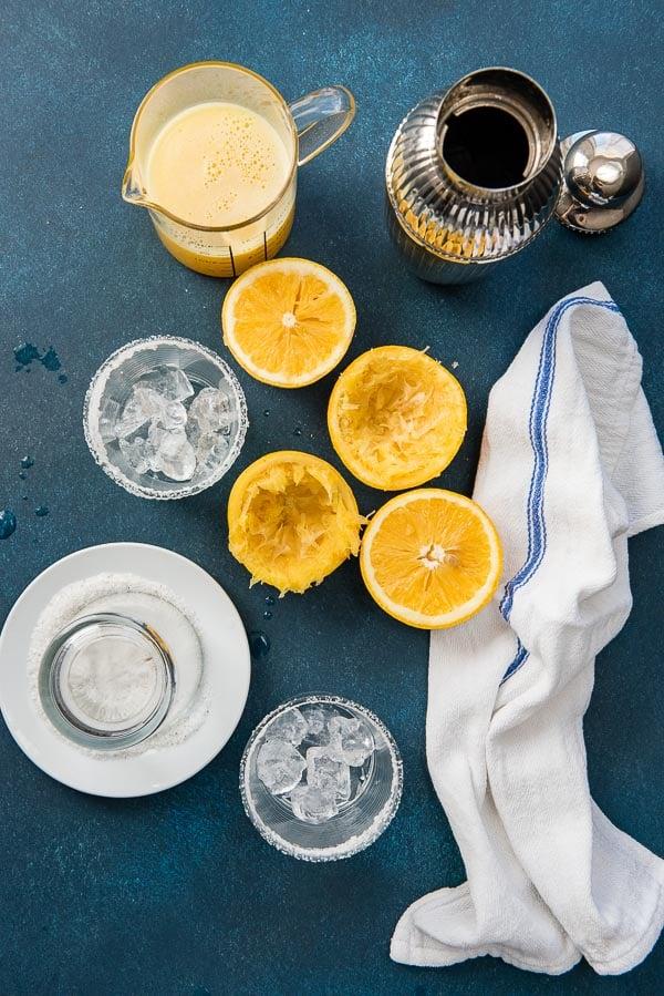 Fresh grapefruit juice, halved grapefruits, salt-rimmed glasses and cocktail shaker for Salty Dog cocktail