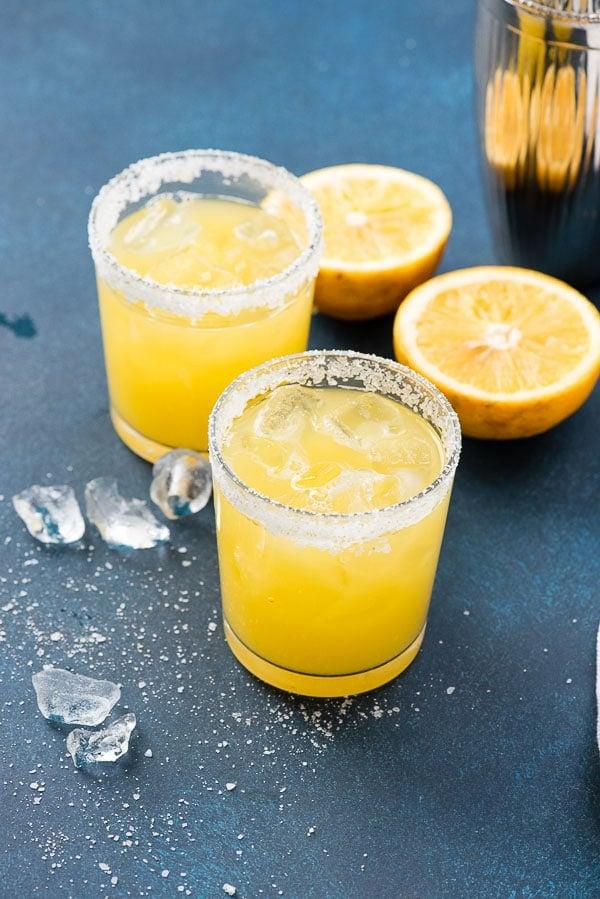 Salty Dog cocktail in salt-rimmed glasses with fresh grapefruit halves