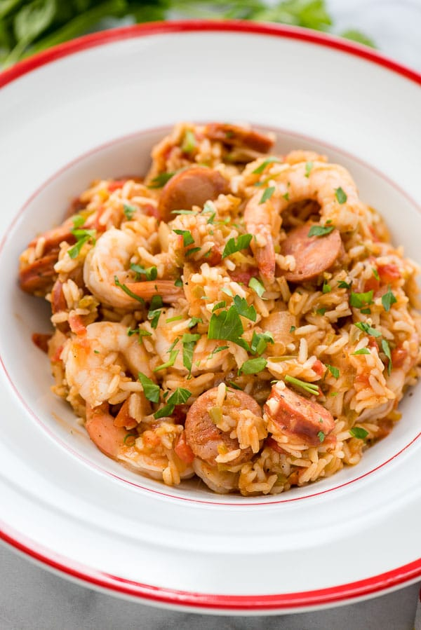 Instant Pot Jambalaya with torn Italian parsley in large white bowl