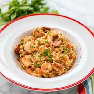 Spicy Instant Pot Jambalaya in white bistro bowl wtih red rim and Italian parsley