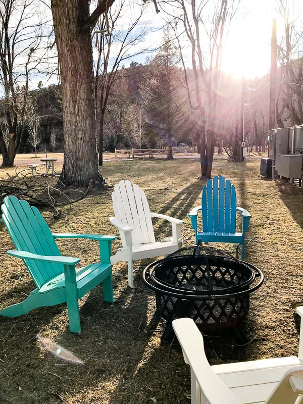 Firepit at WeeCasa Resort with colorful adirondack chairs and a wroght iron fire basket