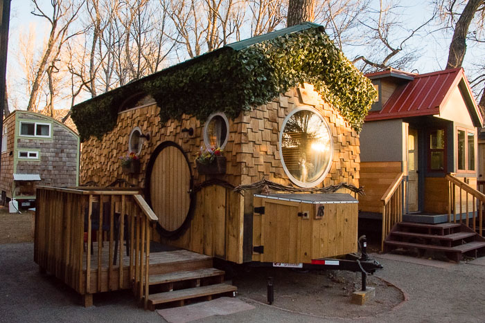 Sunrise at ivy-covered shingled The Hobbit House Tiny House at WeeCasa Tiny House Resort