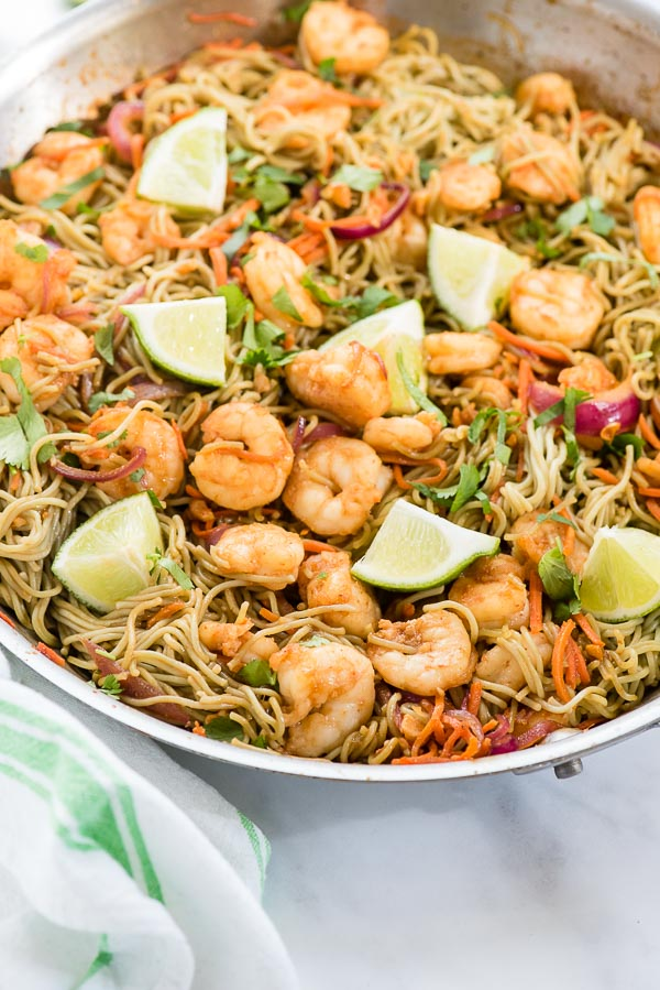 Dragon Shrimp Noodles with lime wedges and green striped towel