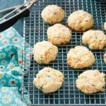 Freshly baked gluten-free Cake Mix Funfetti Cookies on a cooling rack with cookie scoop and flowered cloth