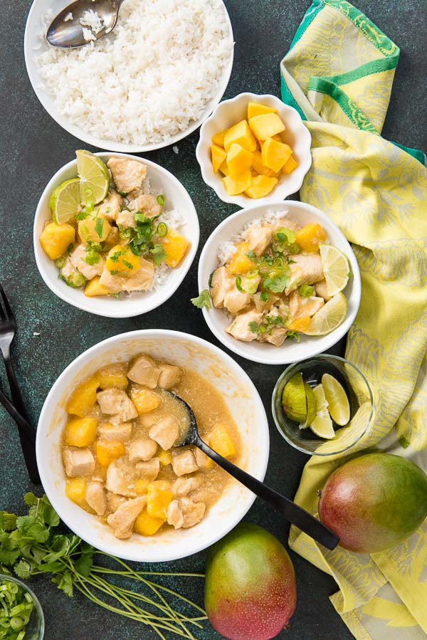 Bowls of Instant Pot Mango Chicken with white rice, cilantro, lime wedges and whole mangoes