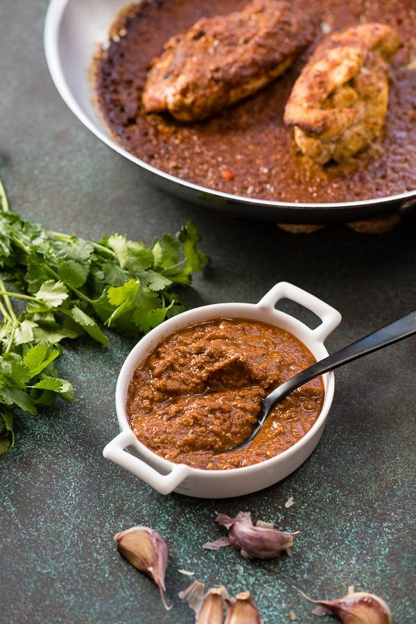 Mole sauce in a white ramekin with black spoon for mole-roasted chicken with fresh cilantro