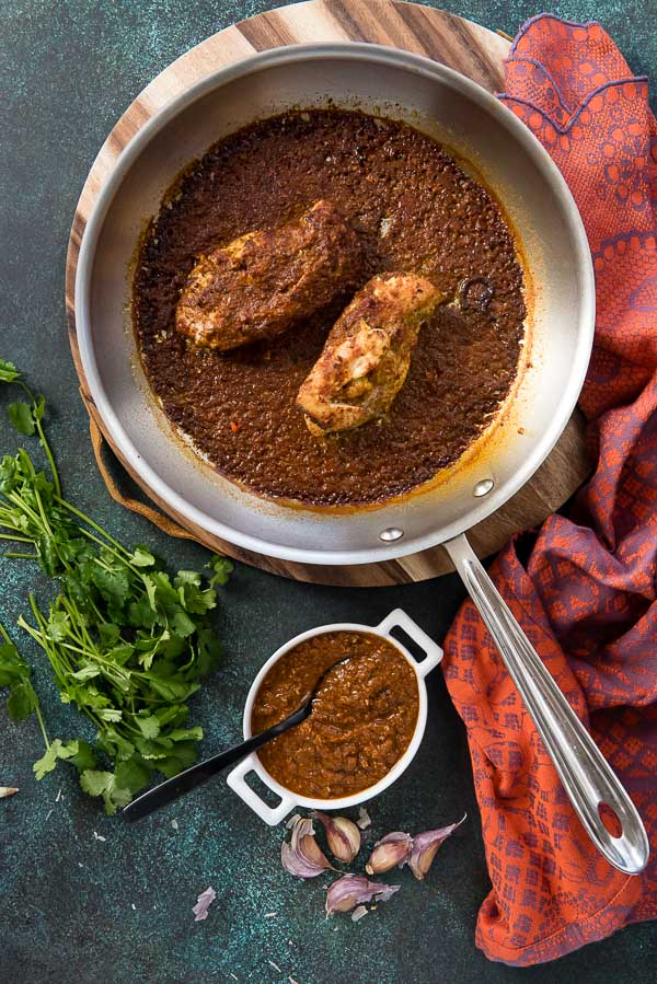 Mole-Roasted Chicken in a large skillet with cilantro. and mole sauce in a white ramekin