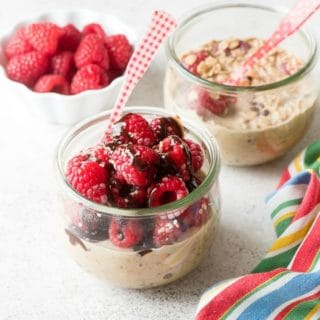 Raspberry Mocha French Vanilla Overnight Oats in glass jars piled high with fresh raspberries, dairy-free chocolate syrup and hemp hulls with red gingham spoon