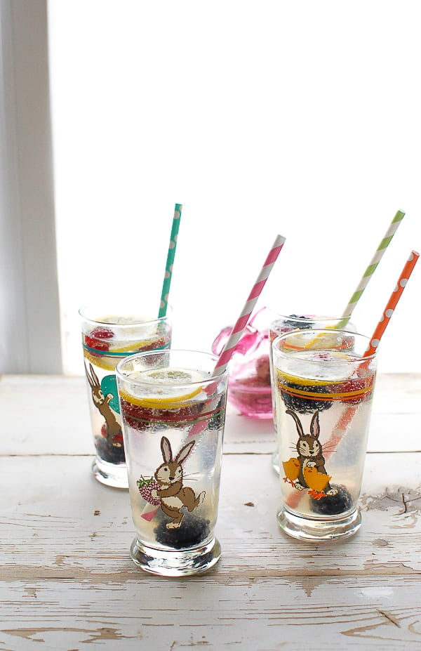 Four Easter-themed highball glasses of Elderflower Gin Fizz cocktails with colorful straws
