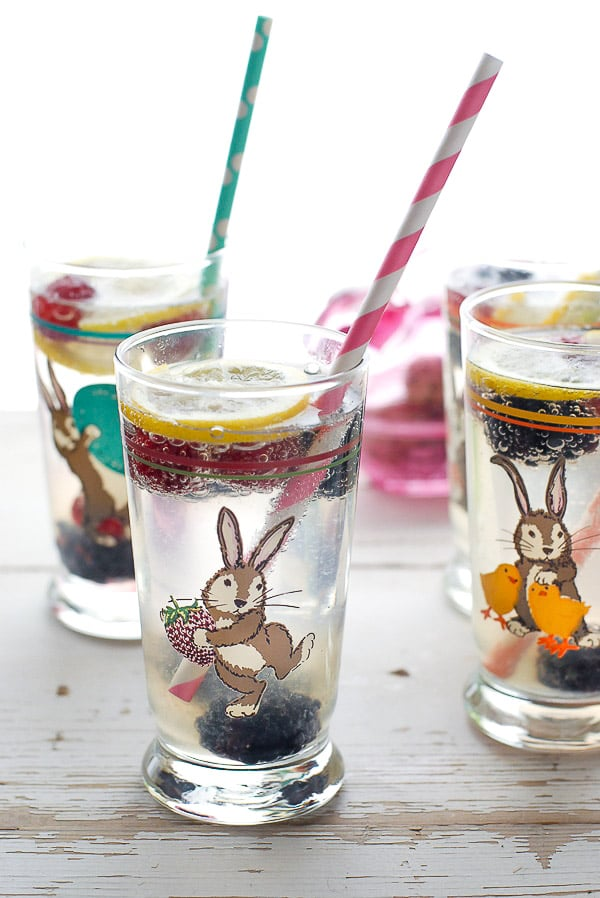 Easter tall glasses with Elderflower Gin Fizz cocktails with lemon slices, colorful straws and frozen berries