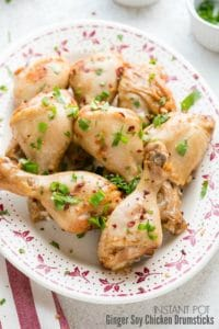 A vintage platter of Instant Pot Ginger Soy Chicken Drumsticks with cilantro, green onion and red pepper flakes garnish