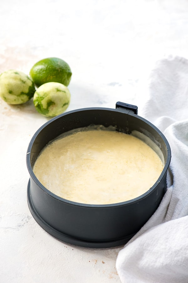 Cooked Instant Pot Lime Cheesecake in silicone springform pan, zested limes in background