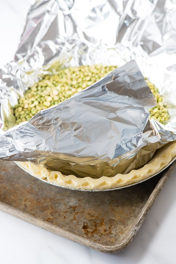 Frozen gluten-free pie crust on baking sheet with foil and beans inside for blind baking crust