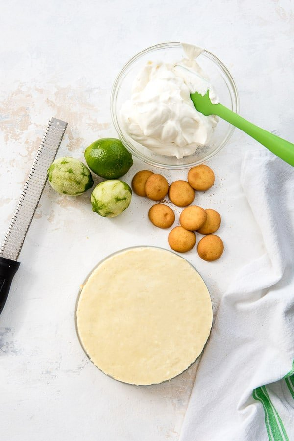 Instant Pot Lime Cheesecake with vanilla wafers, zested limes, microplan and bowl of whipped cream