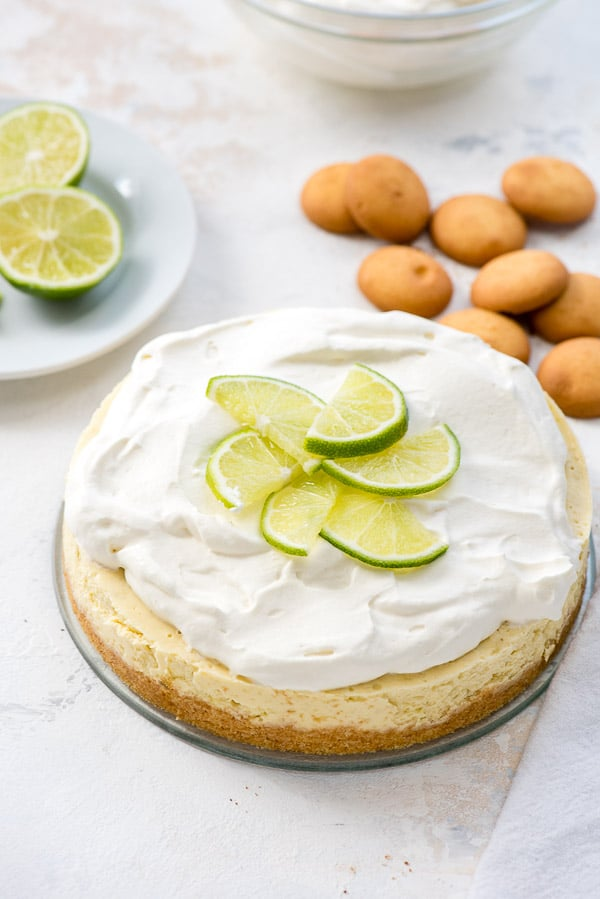 Instant Pot Lime Cheesecake with whipped cream and lime slices on top, vanilla wafers in the background
