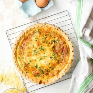 Golden Quiche Lorraine (a cheesy bacon quiche) on a cooling rack with grated cheese and eggs