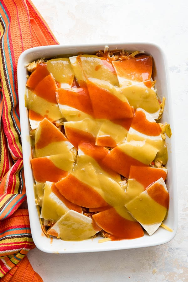 Layered easy breakfast casserole with red and green chile sauce 'christmas-style' on top before baking