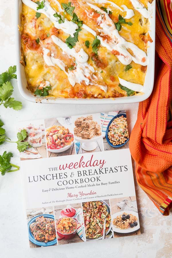 Weekday Lunches and Breakfasts Cookbook and Christmas Breakfast Enchilada Casserole in a white baking dish