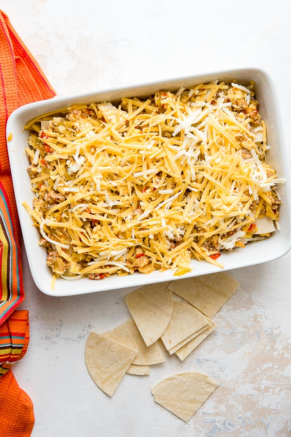 loads of grated cheddar and monterey jack cheese on the top of unbaked Christmas Breakfast Enchilada Casserole