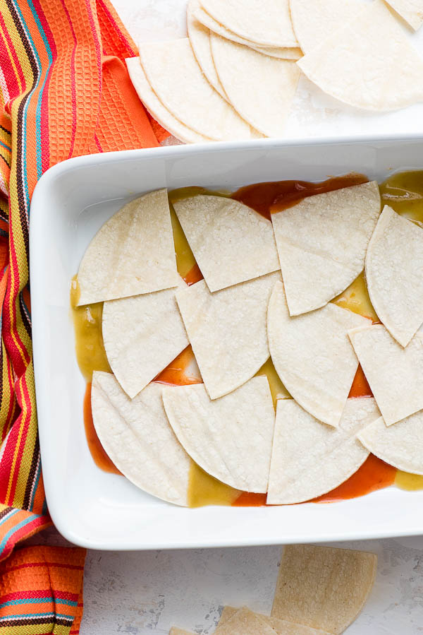 Corn tortilla quarters layered on red and green chile sauce in a white baking dish