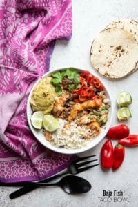 Colorful, spicy Baja Fish taco Bowl with corn tortillas, red chili peppers and lime wedges