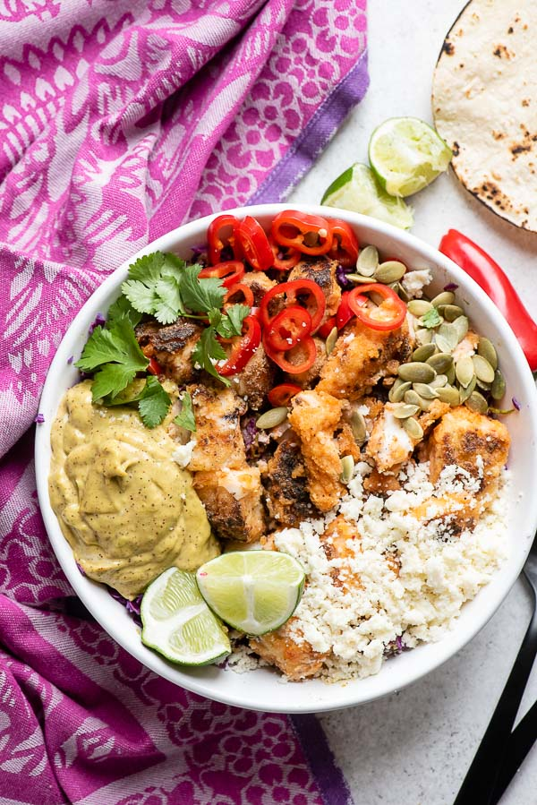 overhead view of Baja Fish Taco Bowl with colorful ingredients and a purple kitchen towel