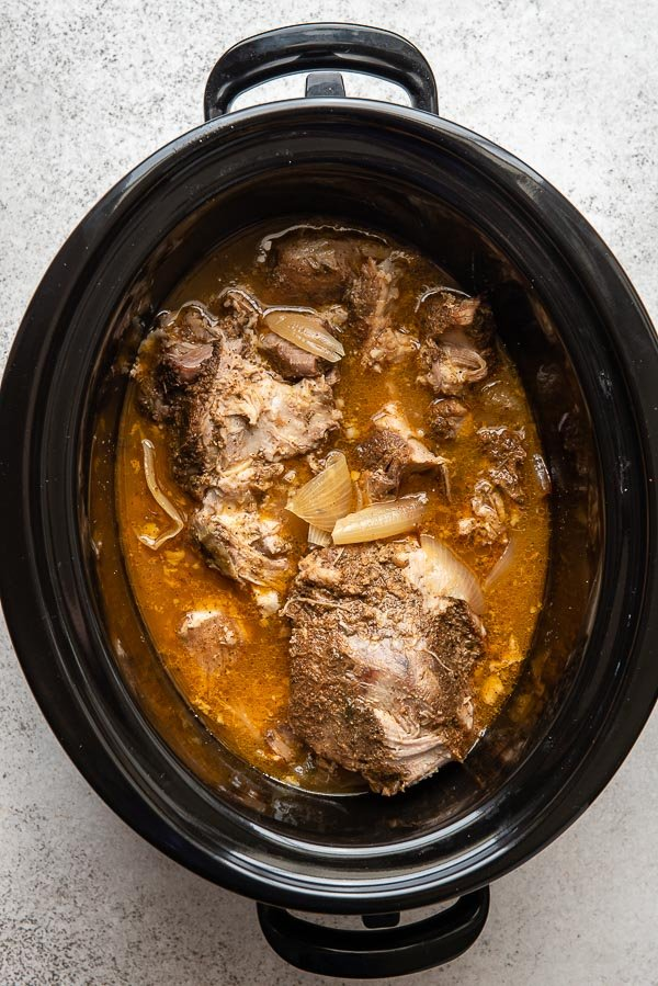 Cooked slow cooker carnitas in a black slow cooker insert with juices