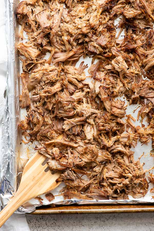 Slow cooker carnitas crisped up after broiling on a sheet pan with wooden spatula