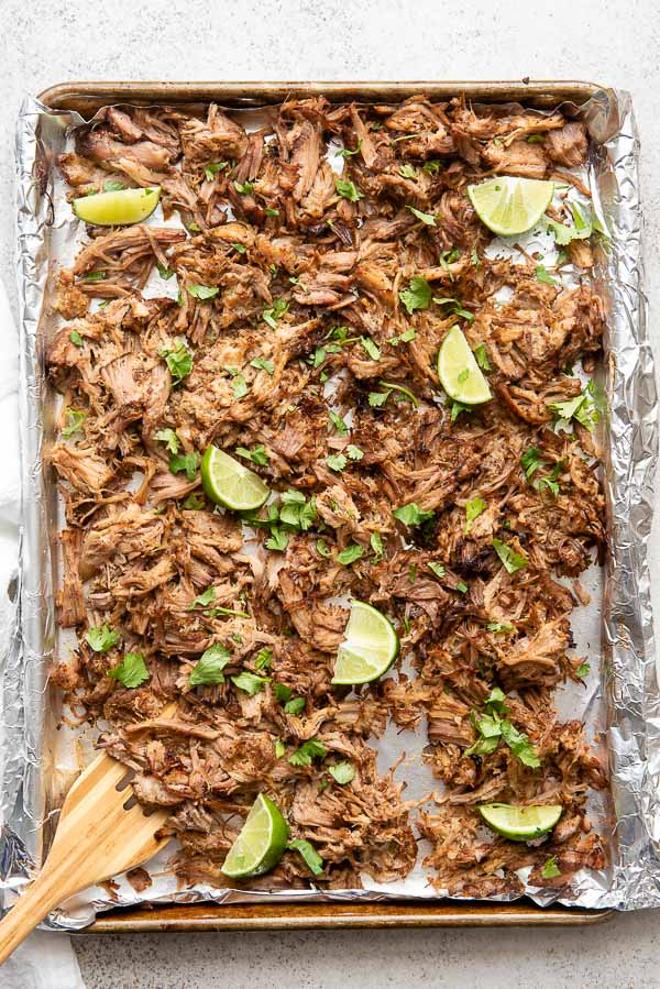 Sheet pan of cooked Pineapple Citrus Slow Cooker Carnitas with cilantro leaves and lime wedges