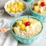 Blue bowls of Instant Pot Pina Colada Steel Cut Oats recipe with pineapple chunks, grated coconut and cherries