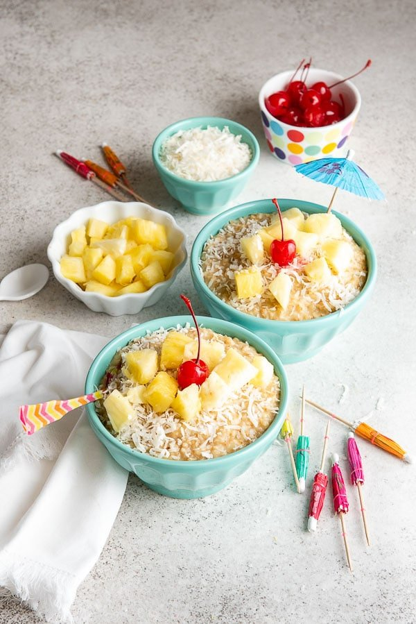 two servings of steaming hot Instant Pot Pina Colada Steel Cut Oats with tropical toppings