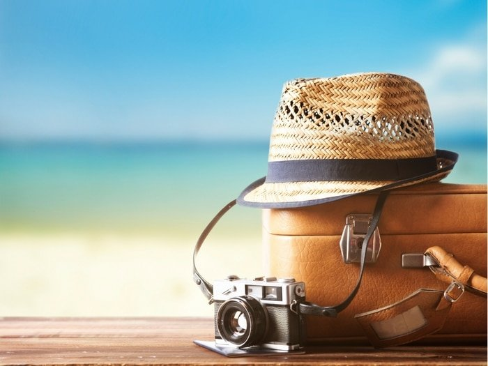 Suitcase, straw hat and camera by the beach