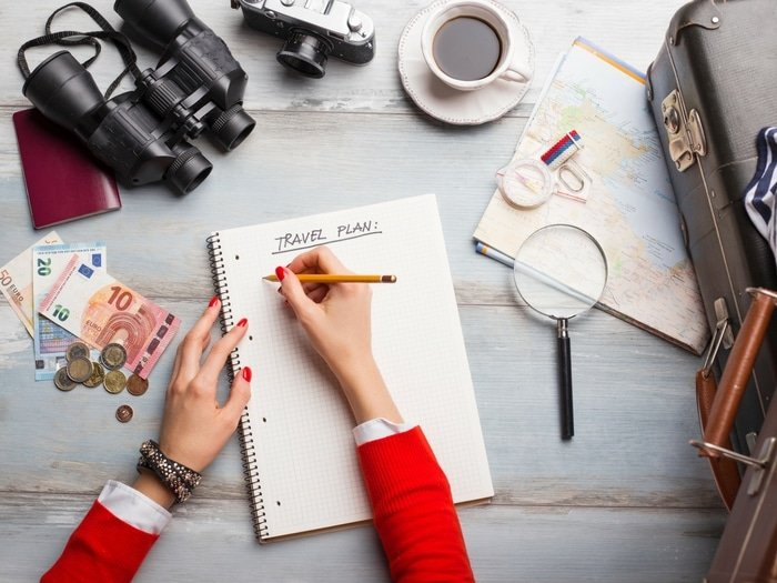 Woman writing a travel plan with travel items around on a desk