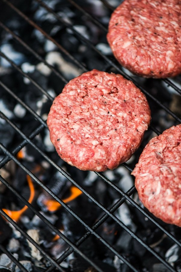 ground beef burger patties on grill uncooked
