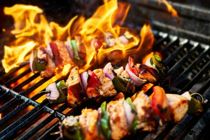 chicken kabobs over fire on grill