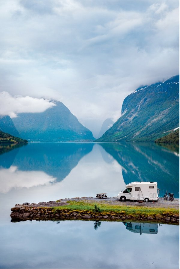 RV camping by a lake with mountains in the background