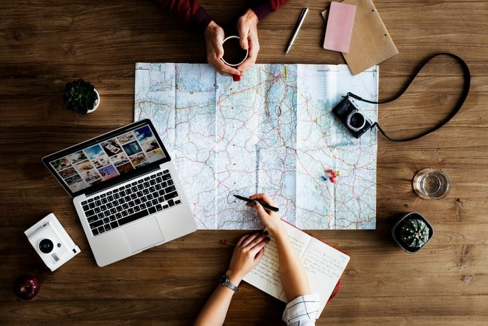 trip planning with map and laptop