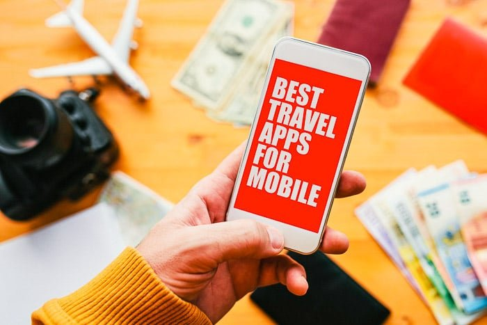 smart phone with 'best travel apps' in person's hand