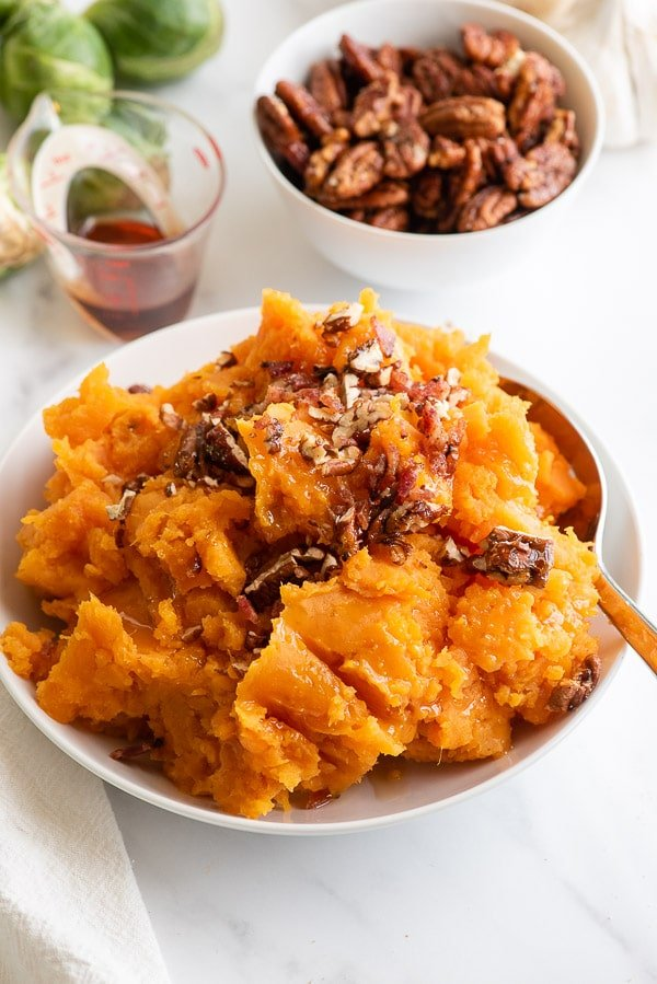 white bowl of mashed sweet potatoes with nuts and bacon on top