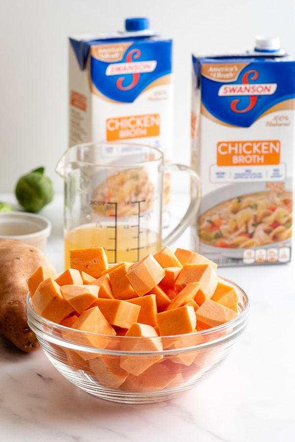 Cubed sweet potatoes in a glass bowl and chicken broth containers