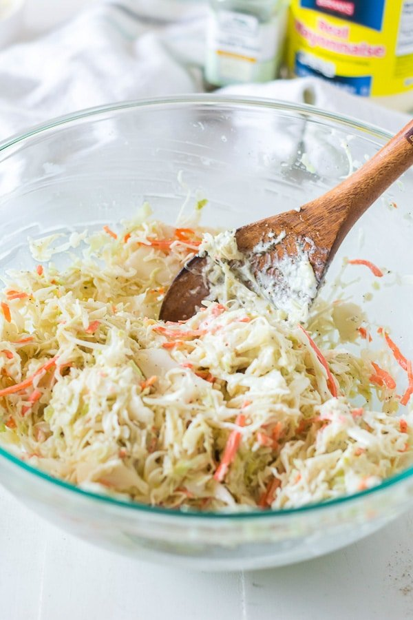 mixing coleslaw in bowl