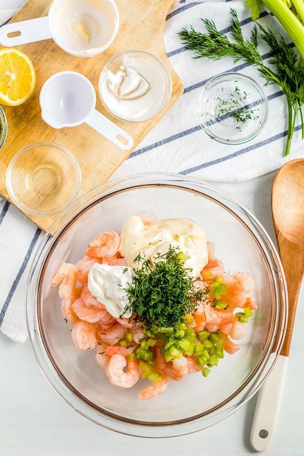 shrimp in bowl with ingredients for shrimp salad