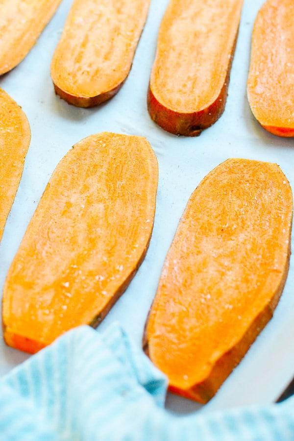 sliced sweet potatoes on a baking sheet