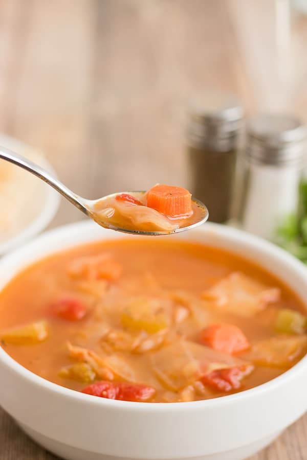 spoonful of cabbage soup over a bowl of the soup