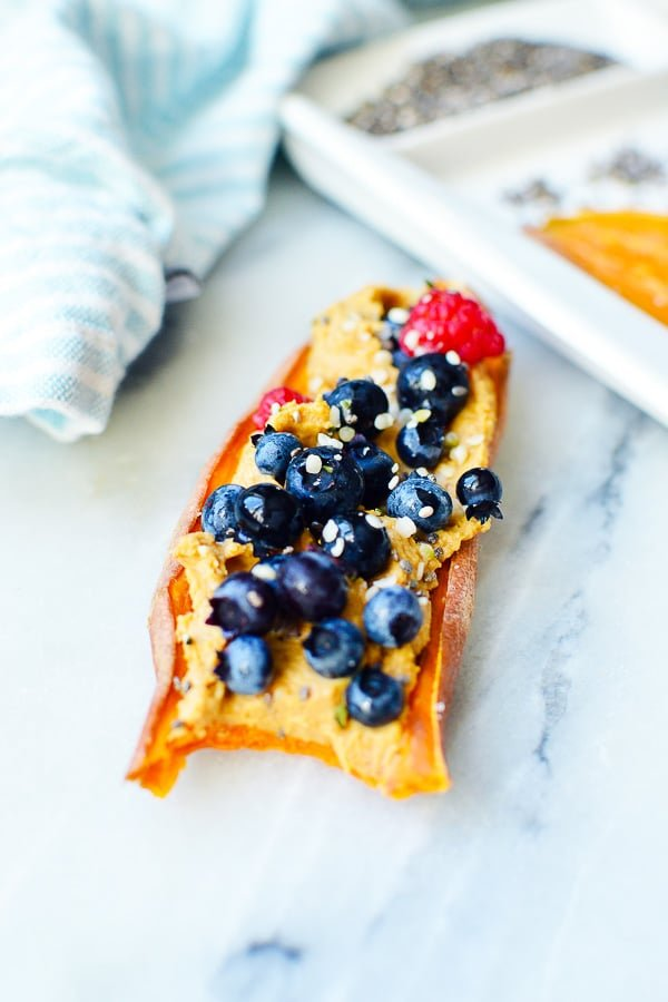 sweet potatoes toast with peanut butter, blueberries and bite taken